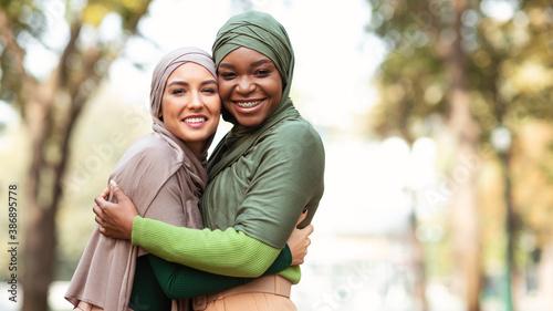 Obraz Two Muslim Ladies In Hijab Hugging Posing Standing In Park - fototapety do salonu