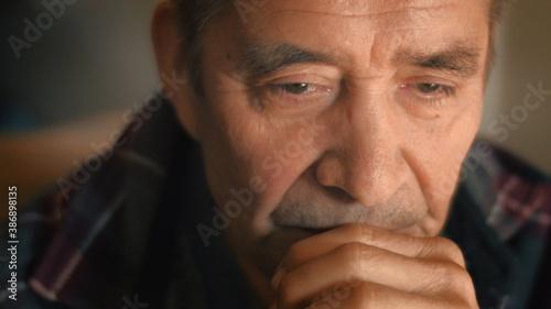 Obraz Sad senior man thinking, looking down. Closeup, shallow DOF. - fototapety do salonu