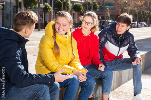 Obraz Four teenagers are talking about play on walk in the park - fototapety do salonu