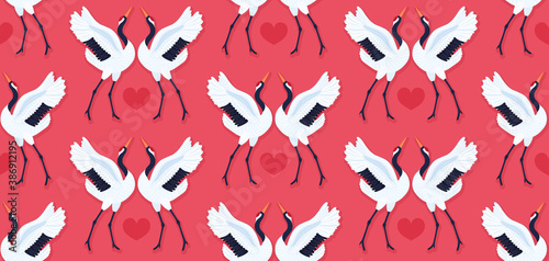 Naklejka premium Seamless pattern with pair of red crowned cranes and heart. Repeating red background with dancing East Asian birds. Love and romance. Valentine's day design. Wallpaper, fabric, wrapping paper. Vector