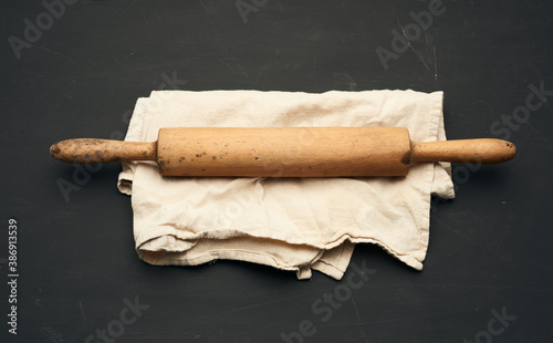 Fototapeta wooden rolling pin lie on a gray linen napkin, black table