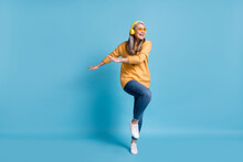 Can't Be Bothered. Full Length Photo Of Charming Dancer Aged Lady Listen Music Earphones Hands Side Knee Up Dancing Clubbing Wear Sunglass Yellow Jumper Jeans Vivid Blue Color Background
