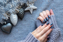 Female Hands In Gray Knitted Sweater With Beautiful Manicure - Dark Gray Blue Glittered Nails On Knitted Background With Silver Tinsel Garland And Christmas Tree Toys: Heart, Star And Pine Cones