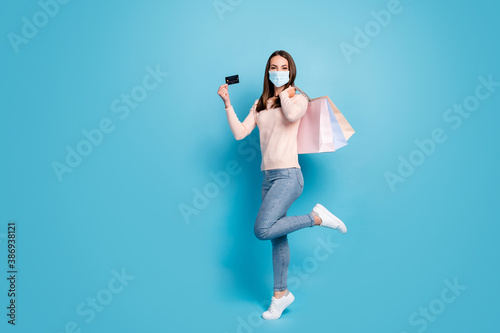 Obraz Full length view of girl jumping carrying new things credit card wear mask isolated shine vibrant blue color background - fototapety do salonu