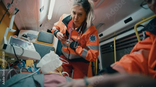 Female and Male EMS Paramedics Provide Medical Help to an Injured Patient on the Way to a Healthcare Hospital. Emergency Care Assistant Inspect the Victim with a Flashlight in an Ambulance. - 386938369