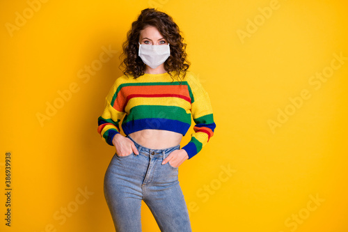 Photo portrait of confident girl with two hands in pockets wear medical mask isolated on bright yellow colored background - 386939938