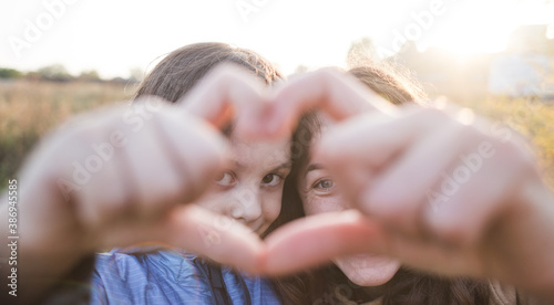 Boy with mom folded fingers in the shape of a heart. Fototapet