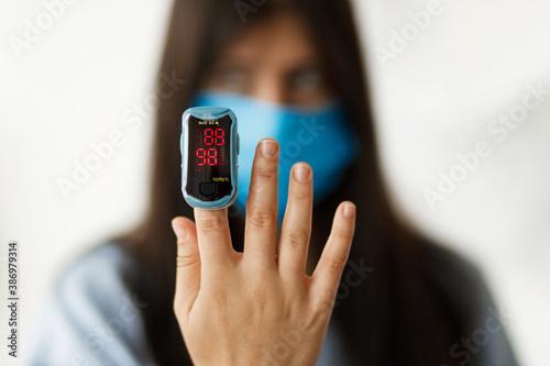 Fotografia Pulse Oximeter on  finger, adult female in face mask measuring blood oxygen leve