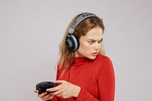 Woman With Headphones Joystick In Hands Playing Games Fun Leisure Lifestyle Entertainment Red Shirt Gray Background