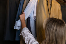 A Woman Inspects A White Shirt She Is Holding By The Sleeve In A Walk-in Closet.