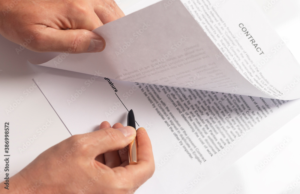 Fototapeta Male hand with pen over document closeup, space for signature. Contract signing concept