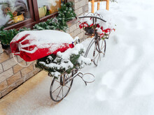 Decorative Forged Bicycle Stands On A Snowy Street Under A Window With Christmas Decor