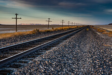 A Nice Landscape Image Of An Old Railroad Track In The Desert With A Telegraph Line Next To It And Mountains In The Background. This Beautiful Image Was Taken During A Gold Hour Sunset.