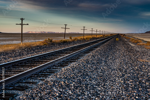 Tela A nice landscape image of an old railroad track in the desert with a telegraph line next to it and mountains in the background