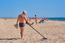 Man With A Metal Detector On The Beach Picks Up A Coin From The Sand
