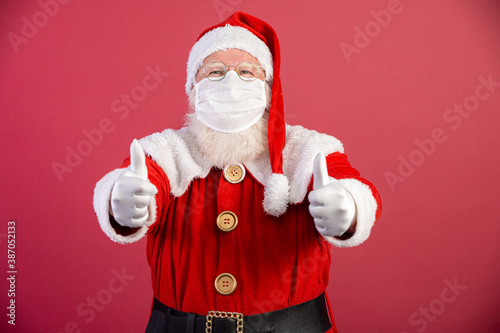 Obraz Real Santa Claus with red background, wearing protective mask, glasses and gloves with thumbs up. Christmas with social distance. Covid-19 - fototapety do salonu