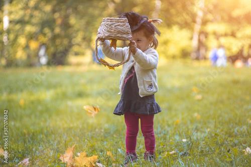 little cute witch flips a basket and pours autumn leaves in the park Tapéta, Fotótapéta