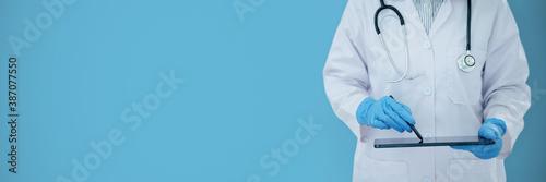 Obraz Medical doctor checking result on digital tablet with empty blue background. - fototapety do salonu