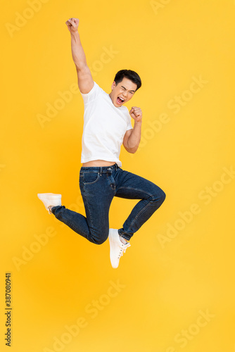 Obraz Young energetic Asian man  jumping and raising his fist isolated on yellow color background - fototapety do salonu