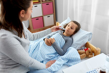 Family, Health And People Concept - Mother And Sick Little Daughter Lying In Bed With Oral Thermometer And Measuring Temperature At Home