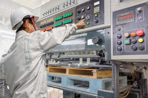 枚葉オフセット印刷機を操作する男性1人の後ろ姿 Fototapet