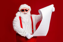 Portrait Of His He Attractive Cheerful Cheery Fat White-haired Santa Father Holding In Hands Wish Present Gift List Isolated Bright Vivid Shine Vibrant Red Burgundy Maroon Color Background