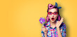 Leinwandbild Motiv Purple head excited very surprised woman with lollipop. Pinup girl in rose pink red glasses with wide opened mouth, eyes. Retro and vintage concept. Yellow orange color background with text copy space