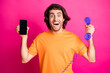 Leinwandbild Motiv Photo of excited guy open mouth hold telephone smartphone screen empty space wear orange t-shirt isolated pink color background