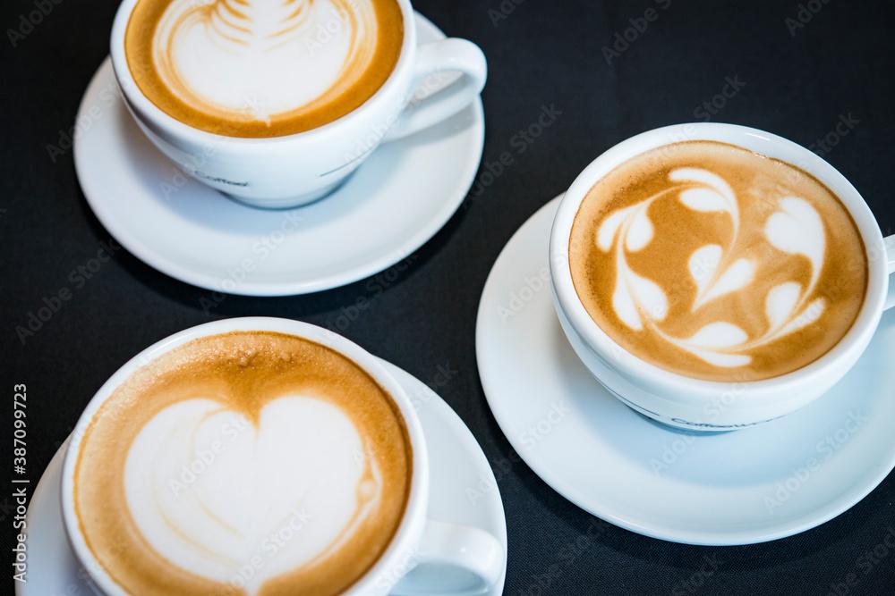 Fototapeta three cups of hot cappucino coffees