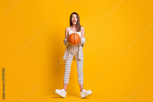 Obraz Full size photo of crazy nice girl hold ball dress tank-top costume sneakers isolated on yellow background - fototapety do salonu