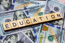 The Word Education On Dollar Usa Background. College Credits, Graduation Funds, Tuition Money Concept.