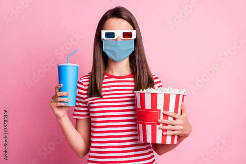Obraz Photo portrait of happy girl wearing 3d glasses holding box with pop corn keeping cup of soda wearing blue face mask isolated on pastel pink color background - fototapety do salonu