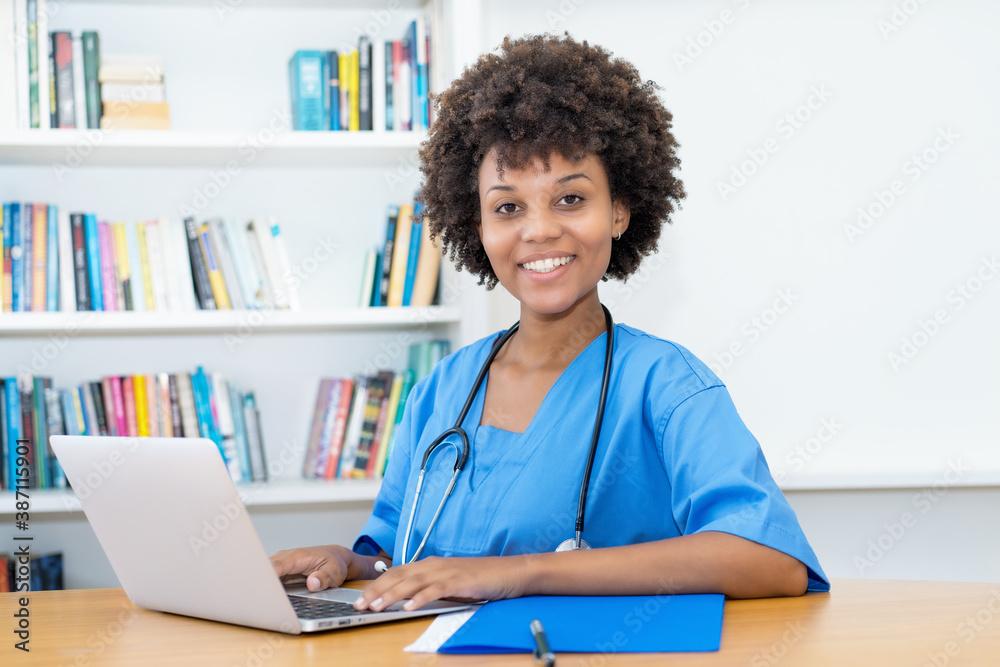 Fototapeta Laughing afro american nurse or medical student at computer