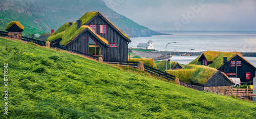 Dramatic summer view of Kirkjubour village with turf-top houses, Faroe Islands,  Denmark, Europe. Beautiful morning scene of Hestur Island. Traveling concept background.