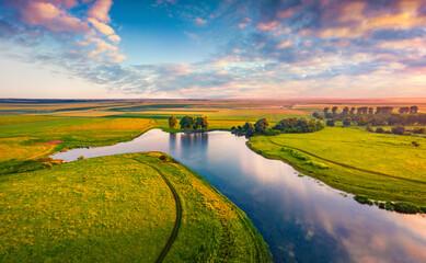 Incredible summer sunrise on Stara Brykulia lake, Ternopil region. Impressive rural scene from flying drone of Ukrainian countryside. Traveling concept background.