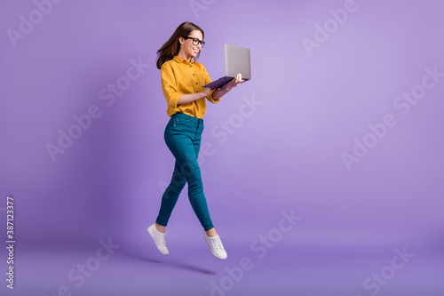 Full length profile photo of lady jump hold netbook look screen wear yellow shirt blue pants sneakers isolated violet color background