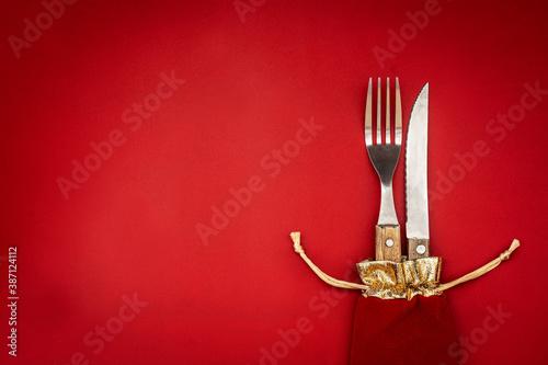 Fork and knife inside of CHristmas bag. Christmas dinner concept Fototapet