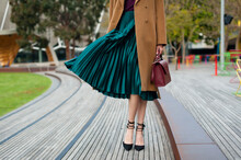 Fashionable Young Woman Wearing Green Pleated Midi Skirt, Sweater, High Heel Shoes, Beige Wool Coat And Holding Burgundy Handbag In Hand On The City Street. Street Style.