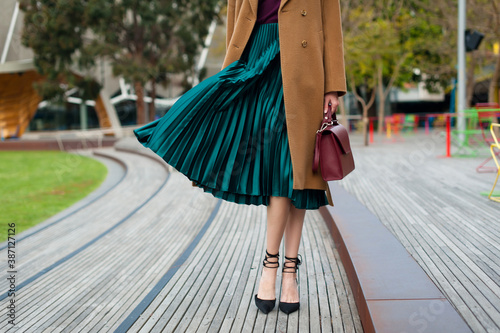Fashionable young woman wearing green pleated midi skirt, sweater, high heel shoes, beige wool coat and holding burgundy handbag in hand on the city street Fototapeta