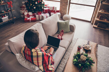 Photo Of Young Lady Sit Couch Hold Computer Legs Typing Wear Plaid Red Socks Jeans In Decorated X-mas Living Room Indoors