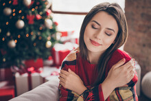 Photo Of Charming Lady Closed Eyes Wrapped Checkered Plaid Hug Herself Wear Red Sweater In Decorated X-mas Living Room Indoors