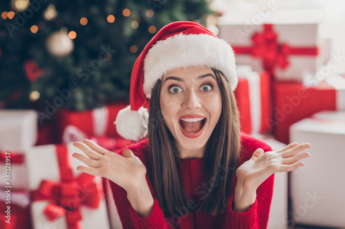 Obraz Photo of shocked young girl gifts hands open mouth staring wear santa headwear red sweater in decorated x-mas living room indoors - fototapety do salonu
