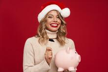 Beautiful Happy Girl In Santa Claus Breaking Piggy Bank