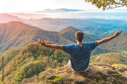 Man sitting on a edge of a cliff and looking at beautiful and rough terrain around him Canvas