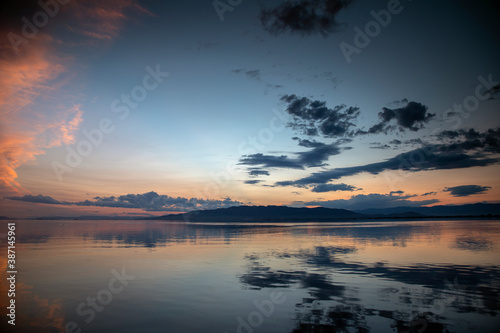 Obraz A sunset over water with clouds - fototapety do salonu