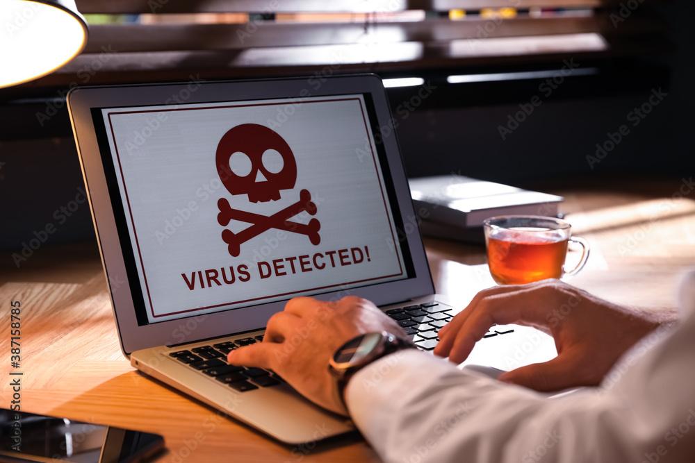 Fototapeta Man using laptop with warning about virus attack at workplace, closeup