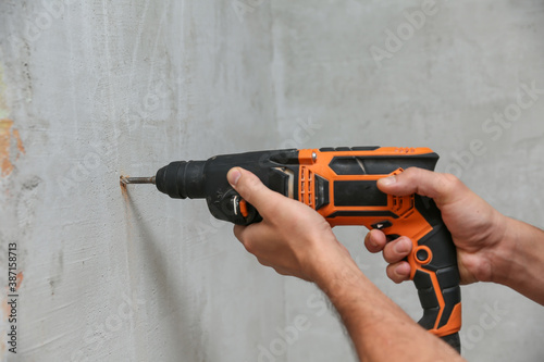 Cuadros en Lienzo person holds hammer drill close up on gray wall background