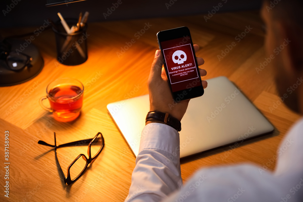 Fototapeta Man holding smartphone with warning about virus attack at table, closeup