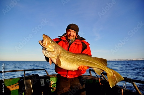 Fotografía A happy fisherman in a red jacket caught and holds in his hands a beautiful huge