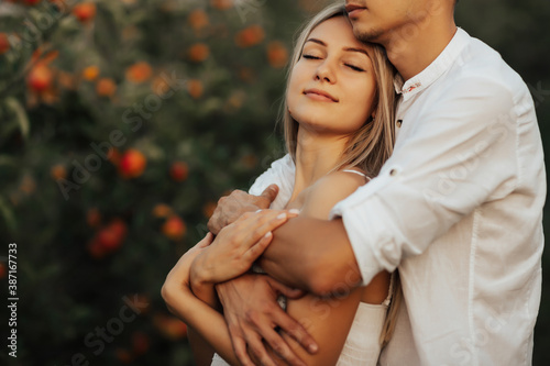 Cuadros en Lienzo Guy in a white shirt hugs from behind a beautiful girl in a white dress in the apples orchard